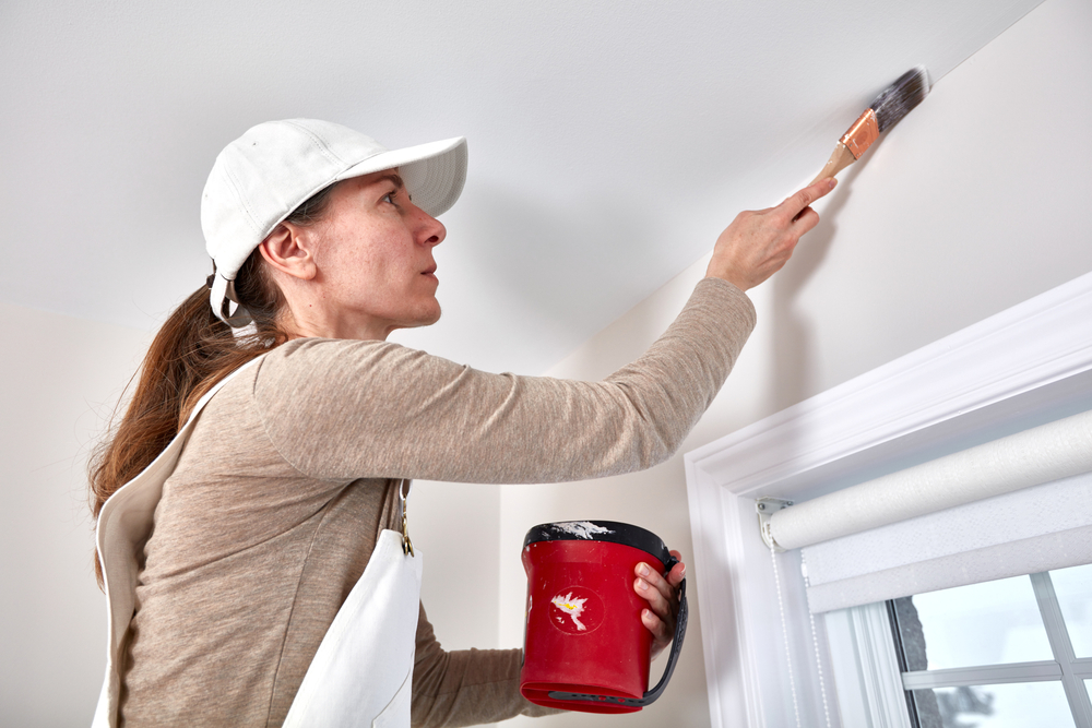Female contractor painting ceiling